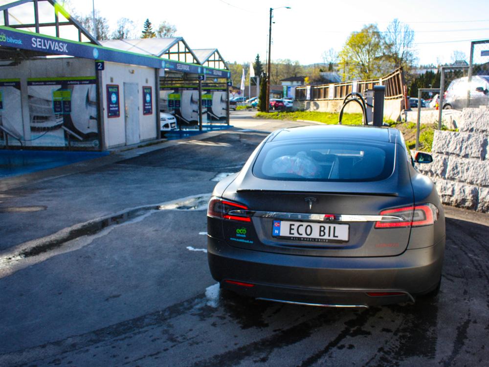 Tesla bakfra vaskehall i bakgrunnen